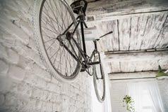 Gammal vit cykelwhist på en vit stenvägg arkivfoto