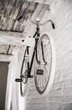Gammal vit cykelwhist på en vit stenvägg royaltyfri foto