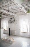 Gammal vit cykelwhist på en vit stenvägg royaltyfria foton