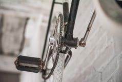 Gammal vit cykelwhist på en vit stenvägg arkivbild