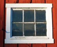 Gammal vit inramat fönster på röd byggnad Arkivbilder