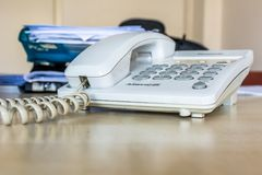 Gammal vit kontorstelefon med kabel Arkivfoton