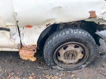 Gammal vit rostig bruten bil av kadavret med fällda ned punkterade hjul med skrapakorrosion och en sönderriven-av stötdämpare fotografering för bildbyråer