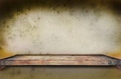 Gammal wood hylla på den grungy väggen Royaltyfria Bilder