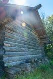 Gammal wood vägg för journalhus med en hög av högg av wood journaler Arkivbild
