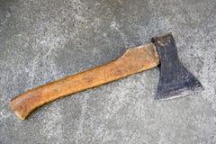 Gammal yxa med ett trähandtag som ligger på det konkreta golvet royaltyfria foton