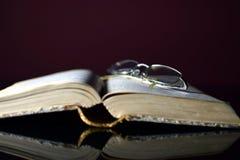 Gammala öppna bok och exponeringsglas Arkivfoto