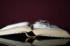 Gammala öppna bok och exponeringsglas Royaltyfria Bilder