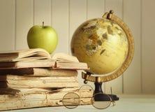 Gammala böcker med äpplet arkivbilder