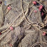 gammala fisknät Gammalt rep som vrids och binds i en packe på en grov träbakgrund Arkivfoto