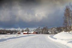 Gammala lantgårdhus i en vinter landskap Arkivbild