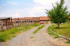 Gammala lantgårdhus, traktor, häst, staket och vägen Arkivfoto