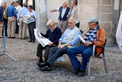 Gammala portugal män på en bänk är avläsningstidningar Arkivfoton