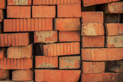 Gammala röda tegelstenar som ligger på måfå Arkivbild