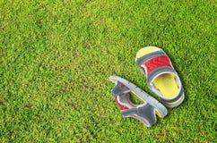 Gammala skor på grönt gräsgolv Arkivbild