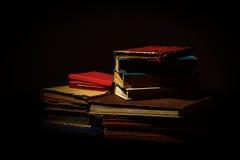 Gammala slitna böcker på black Royaltyfria Bilder