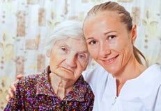 Gammalare kvinna med den unga smileing doktorn Arkivfoton