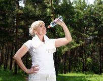 Gammalare kvinna, når att ha övat i skogen Arkivbild