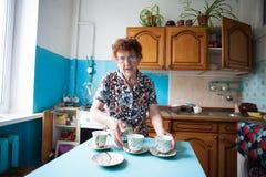 Gammalare kvinna på kök Arkivbild
