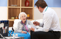Gammalare kvinna som mottar omsorg från brittisk GP royaltyfri foto