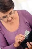 Gammalare kvinnaholdingplånbok med pengar Royaltyfri Bild