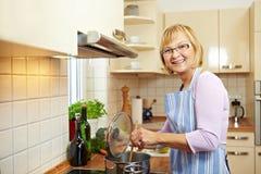 gammalare lycklig kvinna för matlagning royaltyfri foto