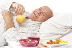 Gammalare man, i att äta för sjukhusunderlag Royaltyfri Foto