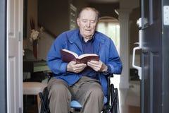 Gammalare man i rullstol som läser bibeln arkivbild