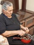 Gammalmodig äldre kvinna som rymmer en kruka med kastanjer och skalar dem royaltyfri bild