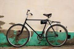 Gammalmodig cykel nära den lantliga gränsen - gul stuckaturvägg Royaltyfria Foton