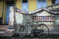 Gammalmodig cykel som lämnas, genom att smula väggen arkivbilder