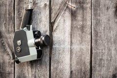 Gammalmodig filmkamera som hänger på träväggen Begrepp - film av 1970sen-1980s fotografering för bildbyråer