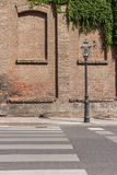 Gammalmodig lampstolpe framme av gammal tegelstenbyggnad arkivbilder
