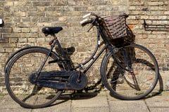 Gammalmodig svart cykel med korgen Arkivbild