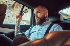 Gammalmodig tatuerad hipstergrabb i en skjorta med hängslen, genom att använda en minnestavla, medan sitta i en lyxig bil på baks arkivfoto