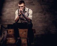 Gammalmodig tatuerad skjorta och hängslen för grabb som bärande vit sitter på träaskar på en studio på mörker arkivbilder