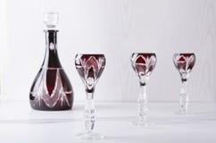 Gammalmodiga exponeringsglas och karaff på den vita tabellen mot den vita väggen Ställ in av glasföremål för aclcoholic drinkar royaltyfri bild