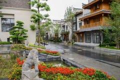 Gammalmodiga kinesiska byggnader i växter och blommor på regnigt D Arkivbilder