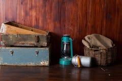 Gammalmodiga lampor för fotogenlykta med oljalampor i ett antikt lagerlager med tappningträenheter vide- korg, royaltyfri fotografi