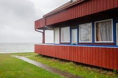 Gammalmodigt sommarhus bredvid lagun i spottade Curonian, Litauen royaltyfri foto