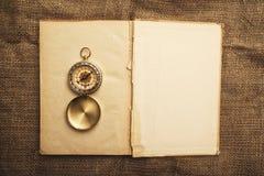 Gammalt öppna boken med kompasset Royaltyfria Foton