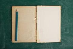 Gammalt öppna boken och blyertspennan Royaltyfri Fotografi