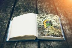 Gammalt öppna boken på en trätabell Tappningsammansättning forntida arkiv Antik litteratur Medeltida och mystisk bakgrund Arkivfoto