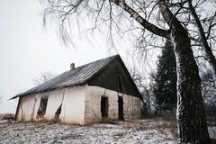 Gammalt övergett hus i vintertid lithuania Arkivfoto