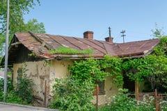 Gammalt övergett hus med ett rostigt metalltak arkivfoton
