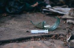 Gammalt övergett hus och använda plast- injektionssprutor Problemet av narkotikaberoende i samhälle arkivfoto