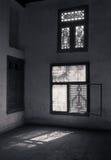 Gammalt övergett mörkt skadat smutsar ner rum med två träbrutna utsmyckade fönster Arkivbilder