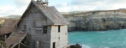 Gammalt övergivet trähus som förbiser havet Arkivfoto