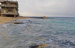 Gammalt översvämmat bogseraskepp och den övergav byggnaden nära kusten Dramatisk sikt av det översvämmade fartyget nära kusten arkivbild