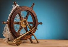 Gammalt ankare för maritimt affärsföretag och gammalt styrninghjul arkivbild